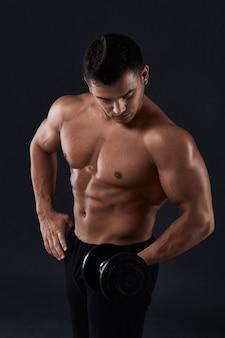 Muskulöser bodybuilder, der übungen mit dummkopf über schwarzem tut starker athletischer mann zeigt körper, bauchmuskeln, bizeps und trizeps heraus arbeiten, das gewicht gewinnen und muskeln mit dummköpfen aufpumpen.