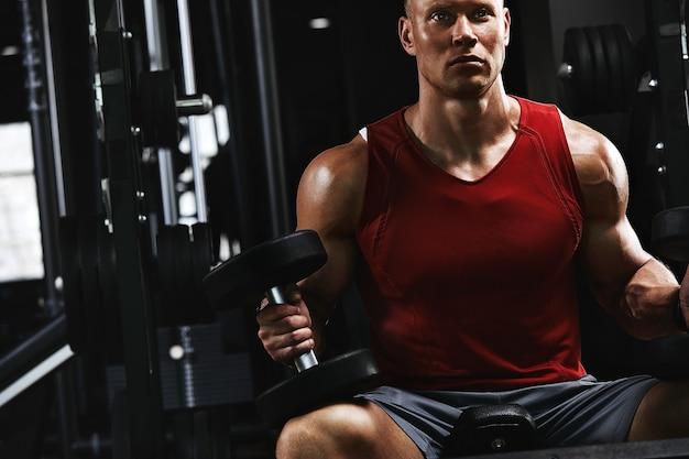 Muskulöser bodybuilder, der übungen mit hanteln aus der nähe im fitnessstudio macht. sportlicher körper, gesunder lebensstil, fitnessmotivation, positiver körper.