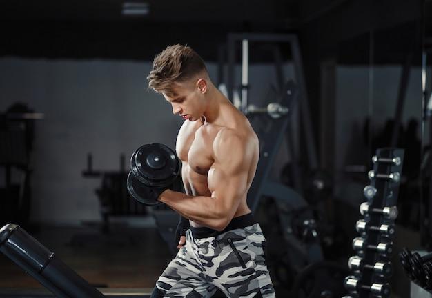 Muskulöser bodybuilder des athleten, der bizepslocke mit dummkopf in der turnhalle ausbildet