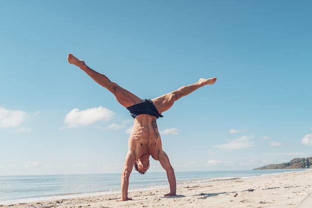 Muskulöser bodybuilder fitness-mann mit nacktem oberkörper steht auf arm am strand
