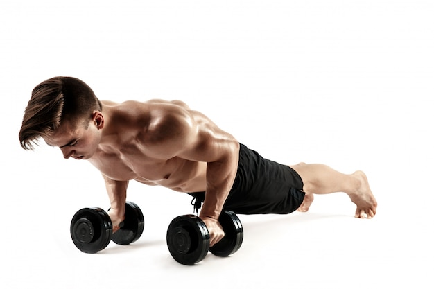 Muskulöser bodybuilderkerl, der liegestütze auf dummköpfen vom boden über weißem hintergrund tut