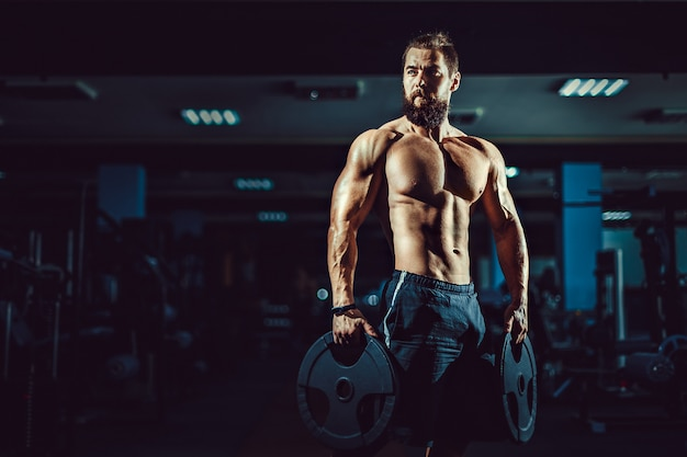 Muskulöser bodybuildermann des athleten, der mit dummköpfen in der turnhalle aufwirft.
