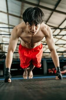 Muskulöser boxer mit schwarzem riemen am handgelenk drückt sich beim aufwärmen nach oben, bevor er im achteck antritt