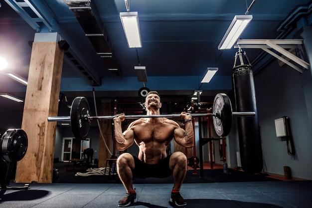 Muskulöser eignungsmann, der kreuzheben ein barbell in der modernen eignungsmitte tut. funktionstraining.