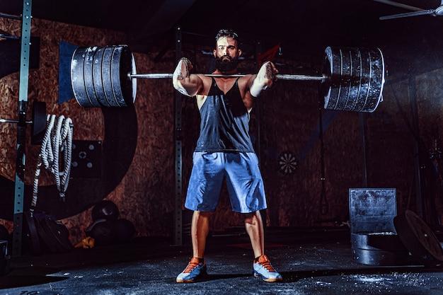 Muskulöser eignungsmann, der kreuzheben ein barbell über seinem kopf in der modernen eignungsmitte tut. funktionstraining.