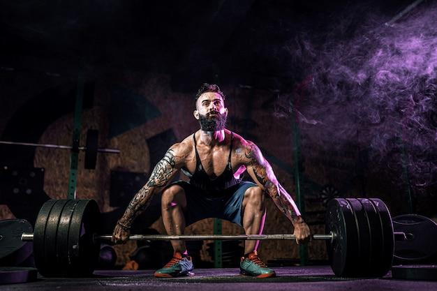 Muskulöser eignungsmann, der kreuzheben eines barbell in der modernen eignungsmitte tut. funktionstraining.