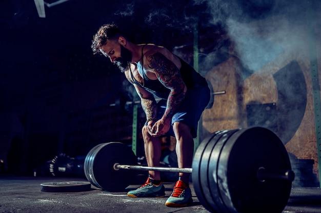 Muskulöser eignungsmann, der zum kreuzheben eines barbell in der modernen eignungsmitte sich vorbereitet. funktionstraining.