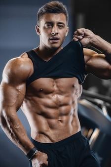 Muskulöser eignungsmann des sports, der an der turnhalle ausarbeitet
