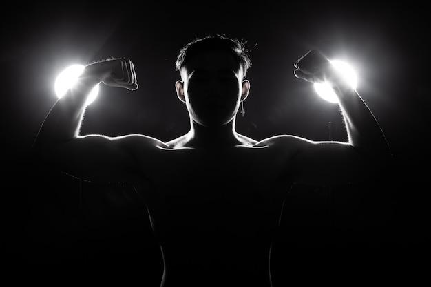 Muskulöser eignungsmann übt gesunden lebensstil im dunklen hintergrundschattenbildrücklicht aus