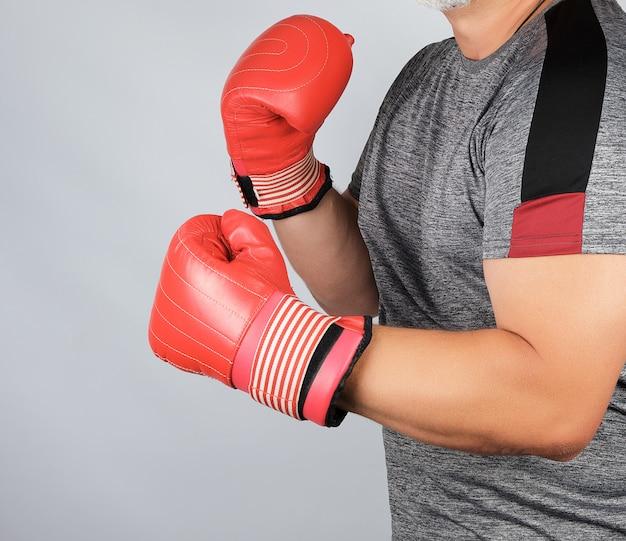 Muskulöser erwachsener athlet in den grauen einheitlichen und roten ledernen boxhandschuhen