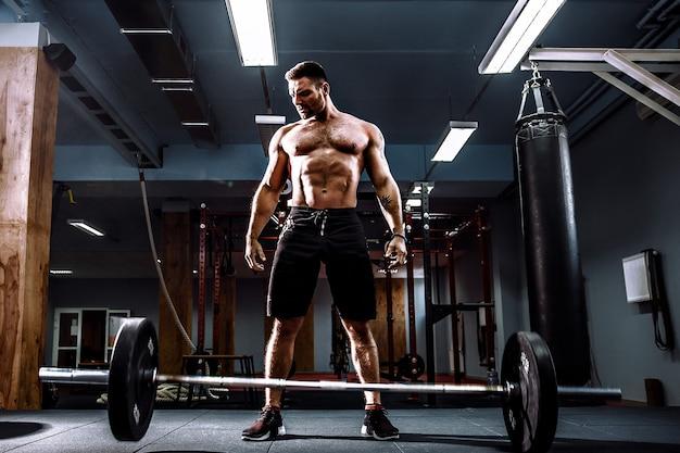 Muskulöser fitnessmann, der vorbereitet, eine langhantel über seinem kopf im modernen fitnesscenter zu heben