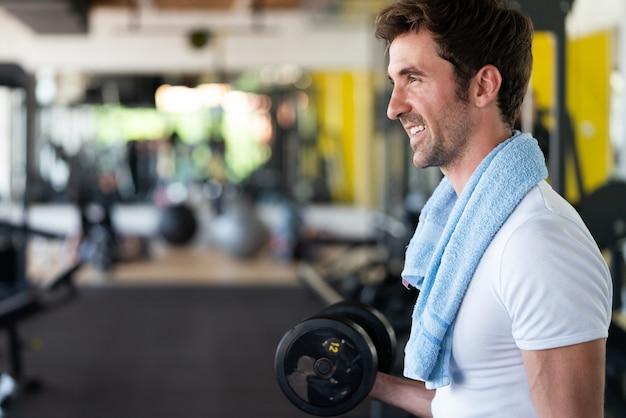 Muskulöser fitter mann, der im fitnessstudio trainiert und übungen mit hanteln am bizeps macht