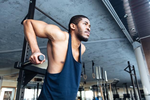Muskulöser fitter mann macht klimmzüge im fitnessstudio mit sportgeräten