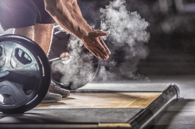 Muskulöser gewichtheber, der vor dem langhanteltraining im fitnessstudio mit hanteln in die hände klatscht.