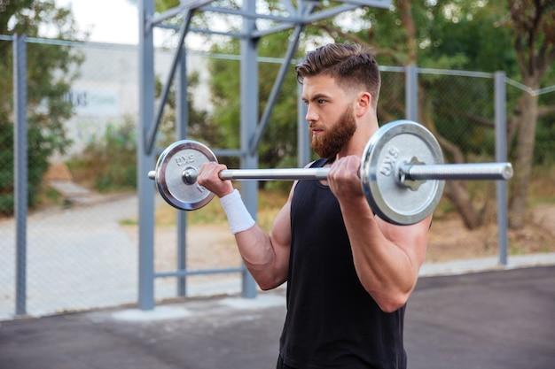 Muskulöser, gutaussehender bärtiger mann training mit langhantel im freien Premium Fotos