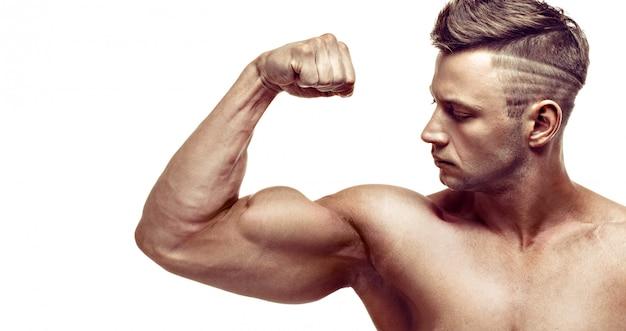 Muskulöser gutaussehender mann, der auf weißem hintergrund aufwirft. zeigt seinen bizeps.
