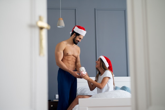 Muskulöser hemdloser mann mit weihnachtsmütze, der seiner freundin im schlafzimmer geschenk gibt.