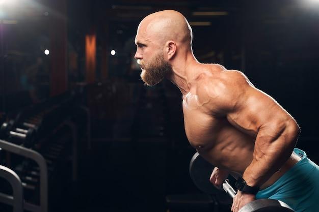 Muskulöser hemdloser sportler, der beim training mit einer langhantel im fitnessstudio entschlossen aussieht looking