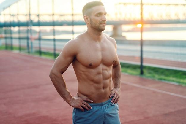 Muskulöser hemdloser sportler, der mit den händen auf den hüften aufwirft, während er am morgen auf dem hofgasthof steht.