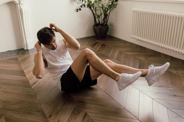 Muskulöser junger, gut aussehender weißer mann trainiert auf dem boden seines hauses und macht eine bauchmuskel-routine...