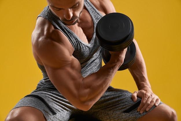 Muskulöser junger herr, der bizeps aufpumpt