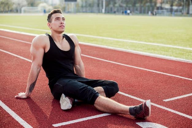 Muskulöser junger männlicher athlet, der auf dem entspannenden leichtathletikfeld sitzt