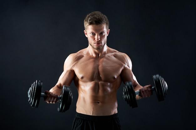 Muskulöser junger mann, der gewichte an schwarzer wand hebt