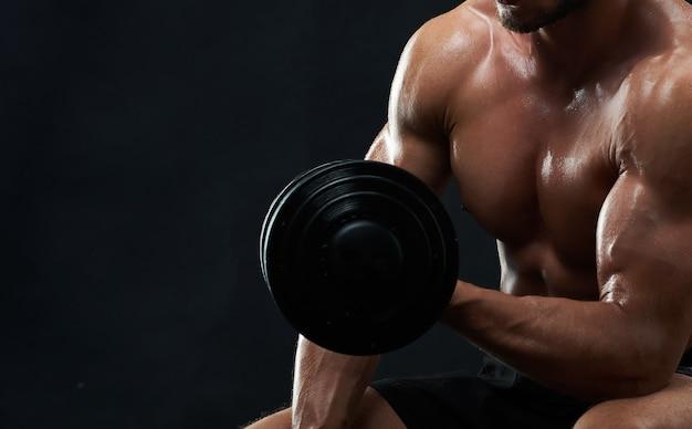 Muskulöser junger mann, der gewichte auf schwarzem hintergrund hebt