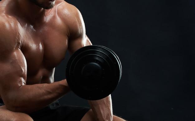 Muskulöser junger mann, der gewichte auf schwarzem hintergrund hebt Premium Fotos