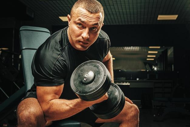 Muskulöser junger mann, der gewichte in einem dunklen fitnessstudio hebt