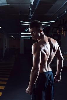 Muskulöser junger mann, der in der turnhalle steht