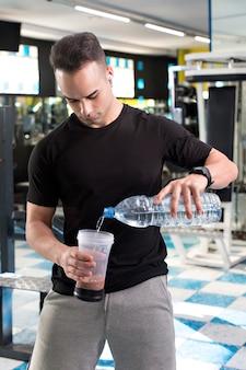 Muskulöser junger mann, der protein-shake vorbereitet.