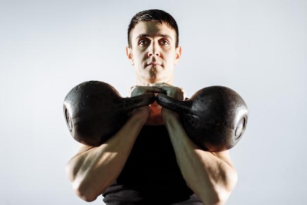 Muskulöser junger mann, der schwergewichts- übung für bizeps tut.
