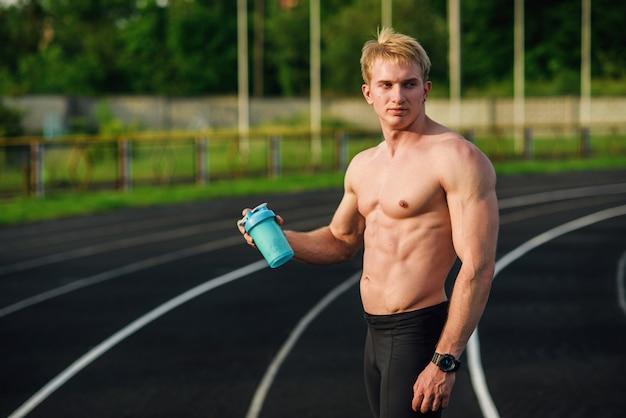 Muskulöser junger mann, der sporternährung in einem schüttler am stadion schüttelt. protein in einer flasche.