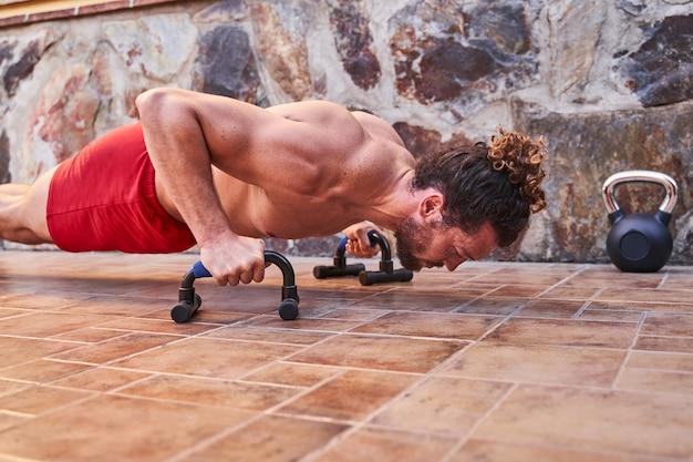 Muskulöser junger mann, der zu hause hochschiebt. heimtrainingskonzept und gesundes leben.