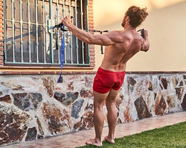 Muskulöser junger mann, der zu hause mit gummibändern trainiert. heimtrainingskonzept und gesundes leben.