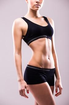 Muskulöser junger sportler der frau, der unten mit ihren händen auf den hüften auf grauer wand schaut