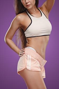 Muskulöser junger weiblicher athlet, der auf fliederraum aufwirft