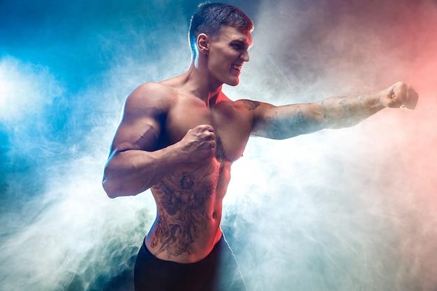 Muskulöser kämpfer, der in der rauch farbszene locht