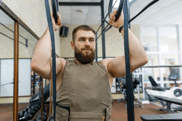 Muskulöser kaukasischer bärtiger erwachsener mann, der übungen tut