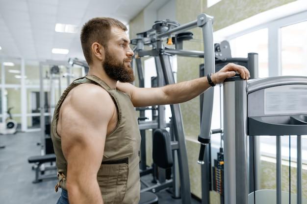 Muskulöser kaukasischer bärtiger erwachsener mann des porträts in der turnhalle