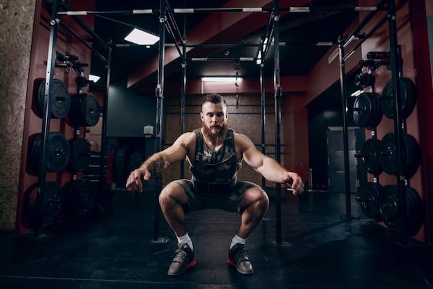 Muskulöser kaukasischer bärtiger mann, der kniebeugen in der gewichteten weste des militärischen stils im crossfit-fitnessstudio tut.