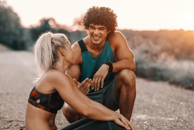 Muskulöser kaukasischer mann mit dunklem lockigem haar, der neben seiner freundin hockt und mit ihr spricht. fitness im naturkonzept.