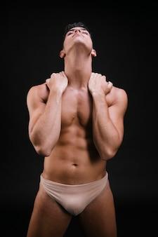Muskulöser kerl, der hals reibt