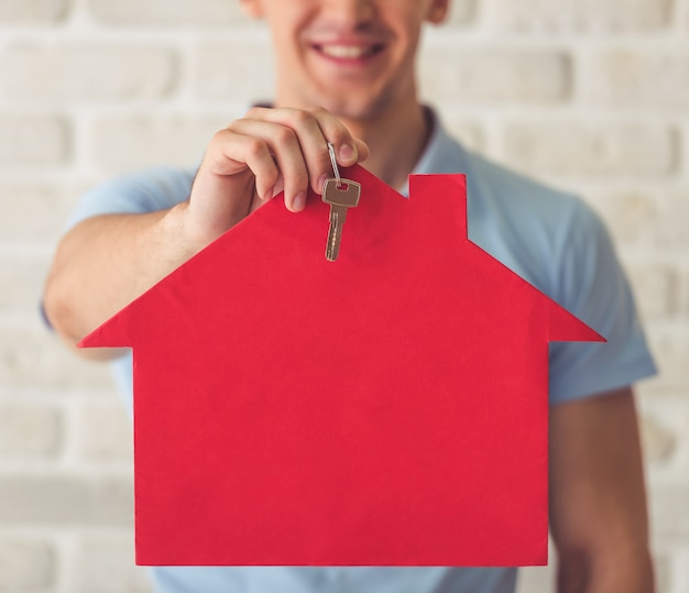 Muskulöser kerl im blauen t-shirt, das ein papierhaus hält