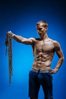 Muskulöser kerl mit ketten auf seinen schultern gegen blau
