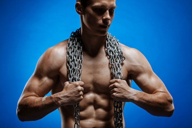Muskulöser kerl mit ketten auf seinen schultern gegen eine blaue wand