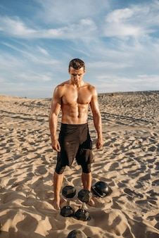 Muskulöser männlicher athlet, der am sonnigen tag übungen mit hanteln in der wüste macht. starke motivation im sport, krafttraining im freien, sportler mit gewichten