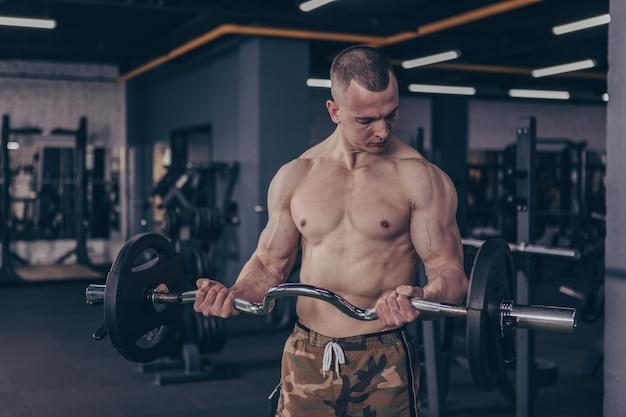 Muskulöser männlicher athlet, der mit barbell am turnhallenstudio ausarbeitet