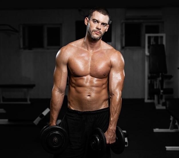 Muskulöser männlicher athlet, der mit dummköpfen in der turnhalle aufwirft